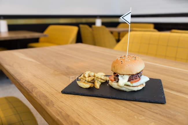 Hamburguesas y papas fritas servidas sobre mesa de madera - foto de stock