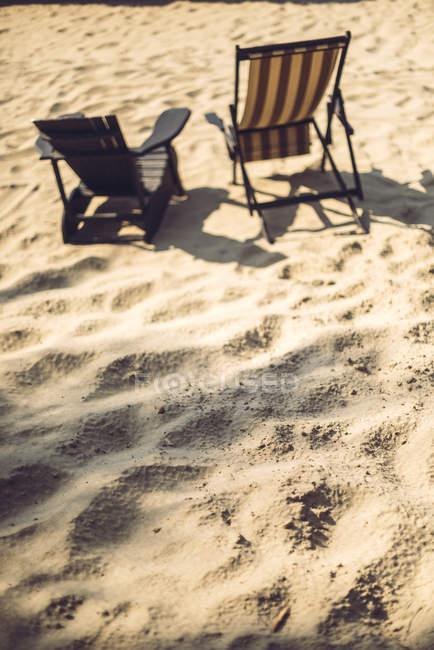 Deux chaises longues sur la plage de sable ensoleillée — Photo de stock
