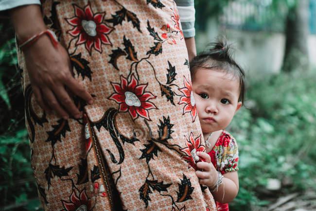 ЛАОС, 4000 ОСТРОВ АРЕЯ: Маленький ребенок смотрит в камеру, прячась за растительной матерью в юбке . — стоковое фото