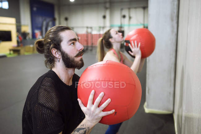 Sporty man and woman exercising with red balls in gym. — Stock Photo