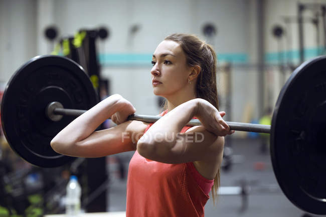 Young fit woman exercising with barbell while working out in  gym. — Stock Photo