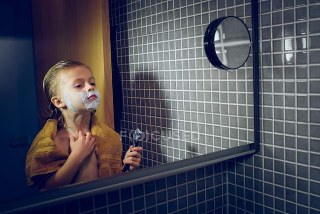 Jovem rapaz confiante de pé no espelho do banheiro e barbear . — Fotografia de Stock