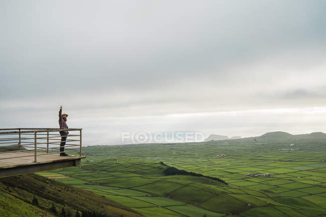 Side view of tourist standing on viewpoint with hand up on background of green fields. — Stock Photo