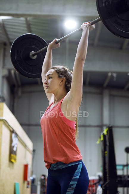 Pretty fit woman lifting barbell at gym — Stock Photo