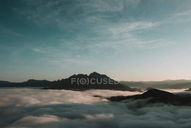 Clouds floating by mountain peaks on sunny day — Stock Photo