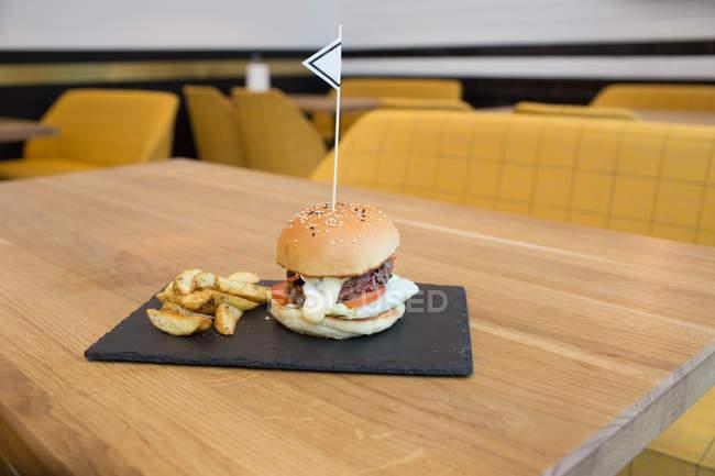 Бургер и картошка подают квадратную тарелку на деревянном столе — стоковое фото