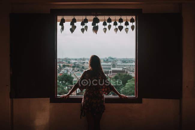 Mulher de vista traseira, olhando pela janela a paisagem urbana — Fotografia de Stock