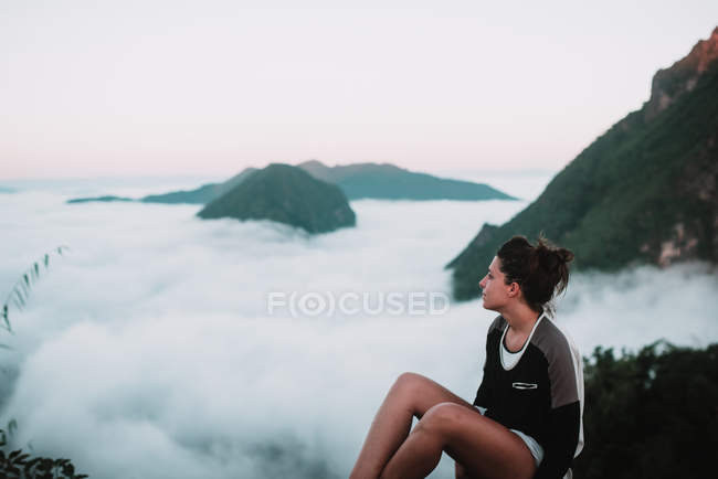 Side view of woman resting on background fog cloud and mountains — Stock Photo