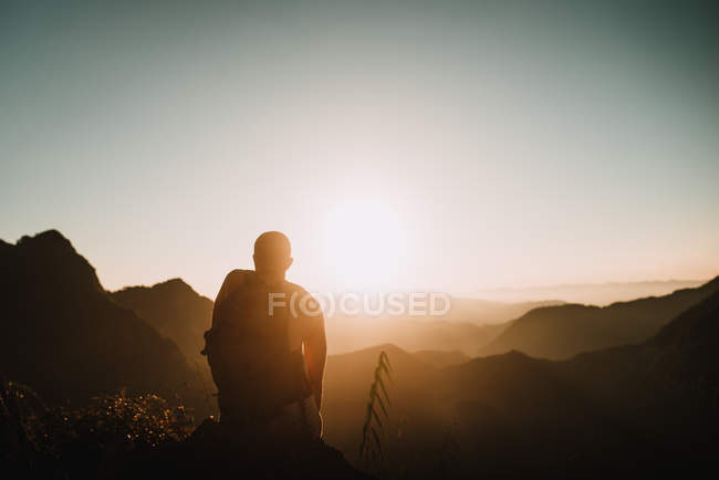 Rear view of backpacker sitting on mountain and admiring wonderful view — Stock Photo