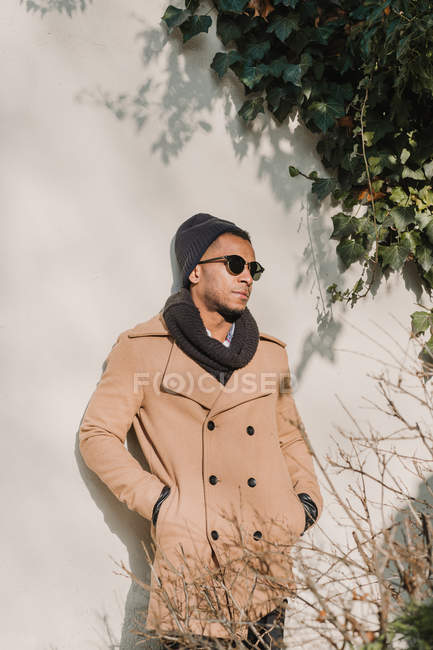Nachdenklicher Mann mit stylischer Sonnenbrille und Mantel an der Wand gelehnt — Stockfoto