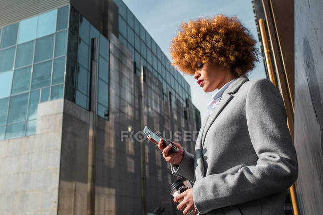 Вид сбоку на стильную женщину, стоящую на улице и просматривающую смартфон — стоковое фото