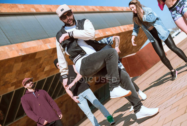 Young friends cheering woman while she performing backflip on city street. — Stock Photo