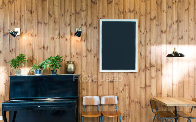 Blank empty blackboard hanging on wooden wall in room with piano and chairs. — Stock Photo