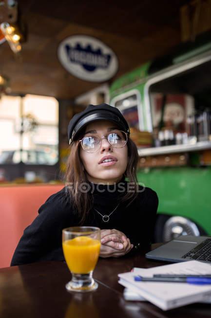 Stilvolle Frau am Tisch gelehnt und Blick in die Kamera — Stockfoto