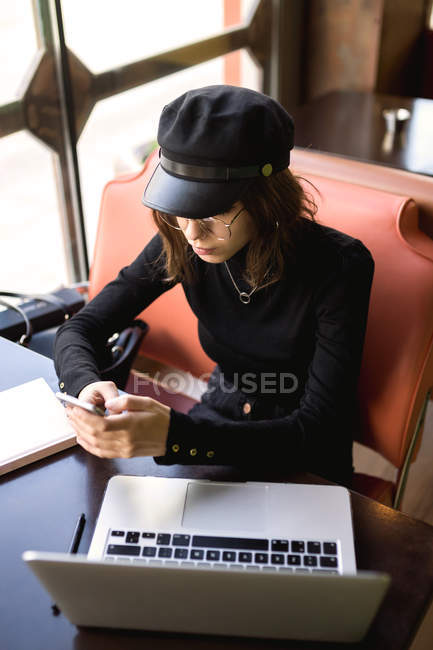 High angle view of stylish woman sitting at laptop and browsing smartphone — Stock Photo
