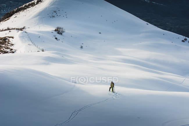 Vue éloignée de personne ski en pente enneigée éclairée — Photo de stock