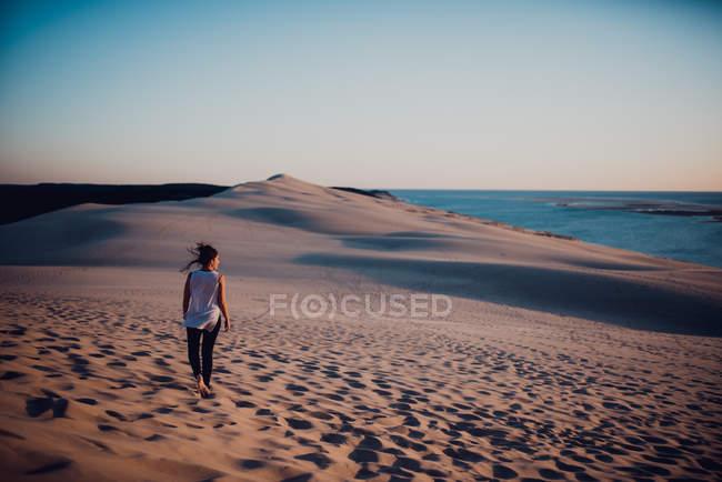 Vista posteriore della donna che cammina sulla sabbia e che osserva da parte — Foto stock