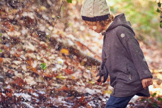 Веселий молодий хлопчик грає з Осіннє листя в сонячний день. — стокове фото