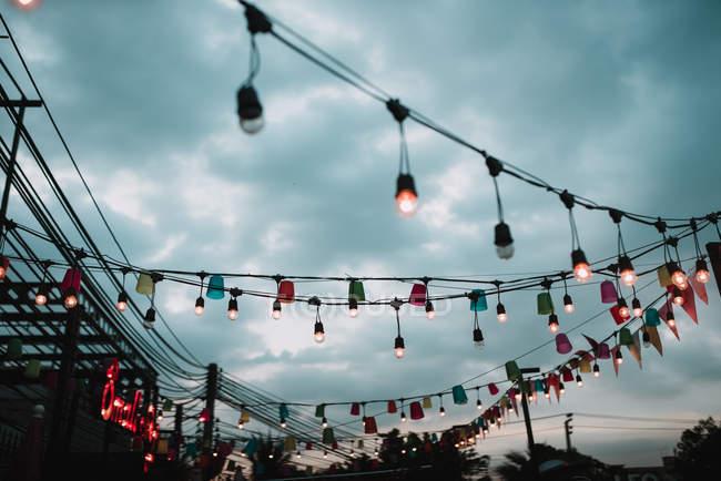 Luzes bonitas penduradas em postes sobre céu nublado — Fotografia de Stock