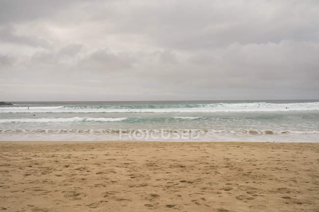 Seascape of sandy coast and wavy ocean in cloudy day. — Stock Photo