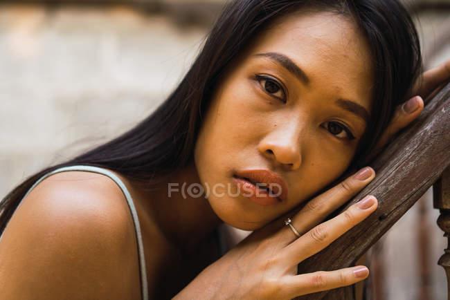 Продуманий жінка, спираючись на дерев'яними поручнями і дивлячись на камеру — стокове фото