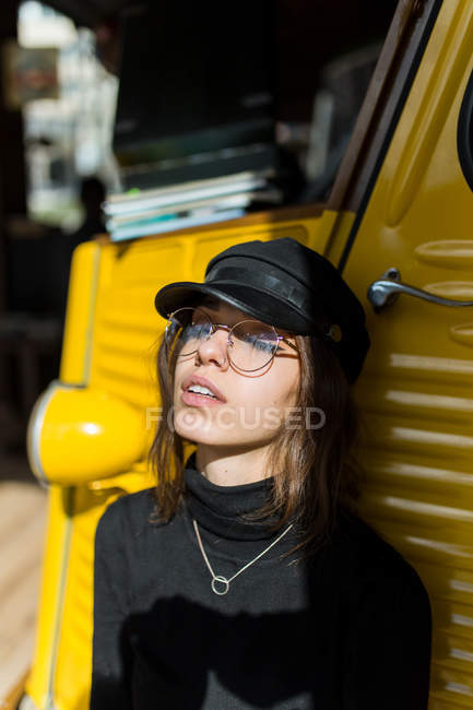 Stylish girl  in glasses and cap leaning on yellow car with eyes closed. — Stock Photo