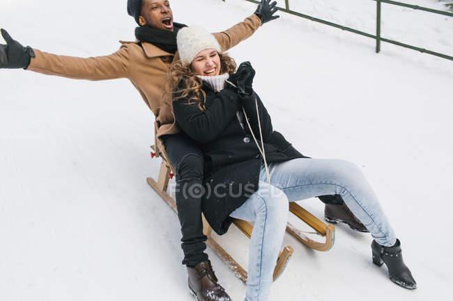 Happy couple riding sledge on snow — Stock Photo