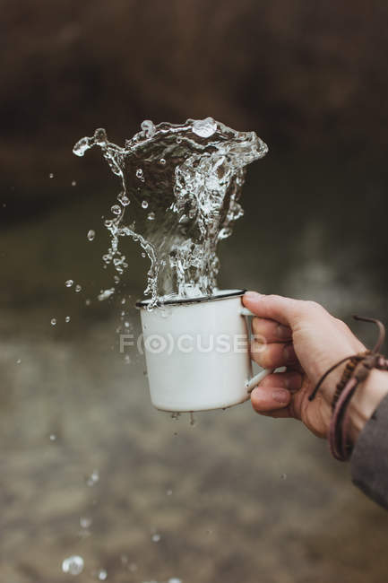 Main, projections d'eau de la tasse blanche — Photo de stock