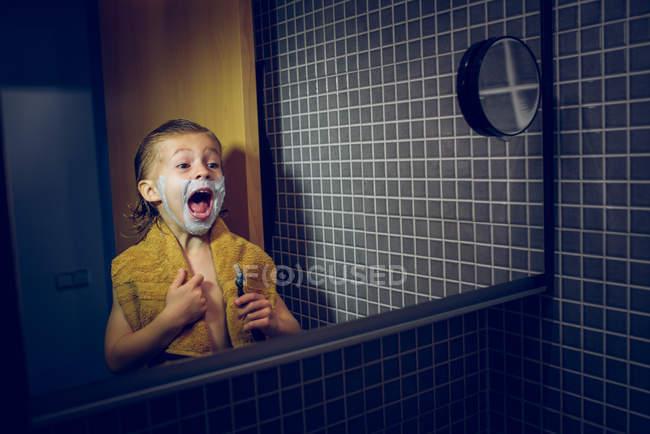Мальчик бреется перед зеркалом и кричит: — стоковое фото