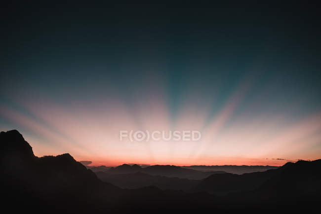 Scenic view to sunset beams in dusk sky over mountains — Stock Photo