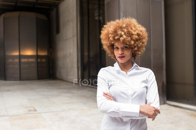 Donna fiduciosa in piedi con le braccia incrociate e guardando la fotocamera . — Foto stock
