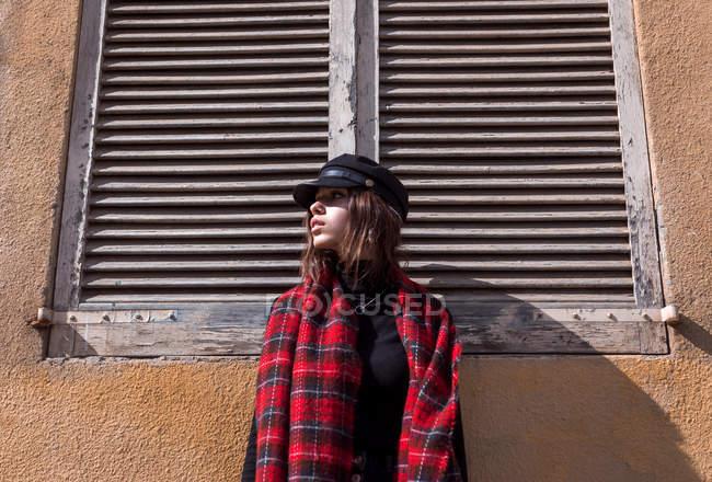Junge Frau mit Mütze lehnt an Wand — Stockfoto