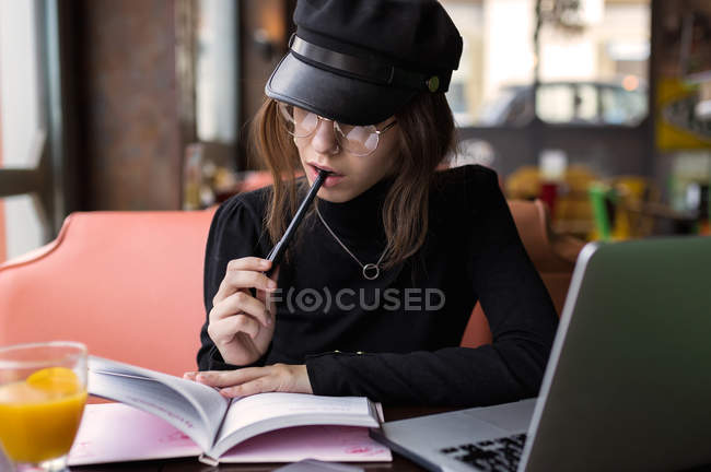 Woman with pen in mouth looking at notebook — Stock Photo