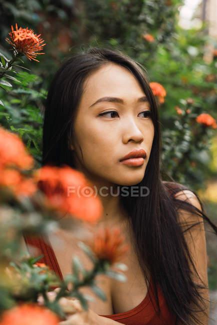 Sinnliche Frau, die am blühenden Busch steht und wegschaut — Stockfoto