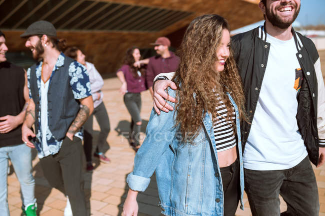 Cheerful young group of people walking and communicating on pavement. — Stock Photo