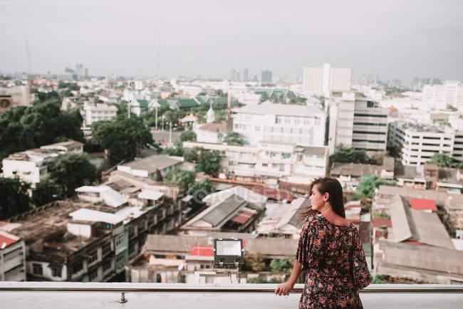 Вид сзади женщина позирует на городской пейзаж и глядя — стоковое фото