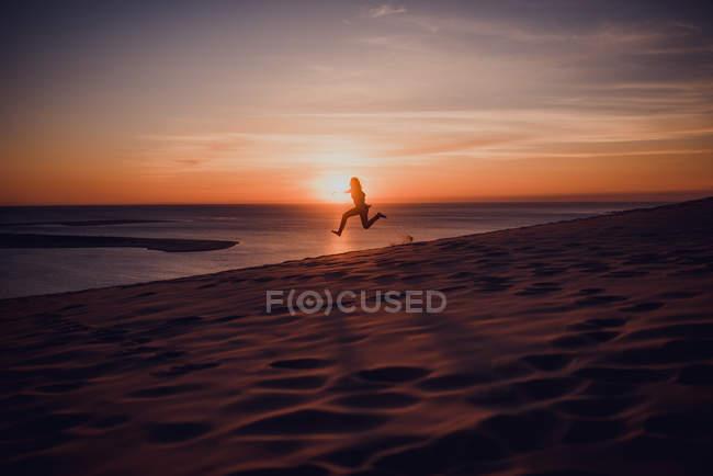Silhouette de femme sautant en l'air sur la plage de sable au coucher du soleil — Photo de stock
