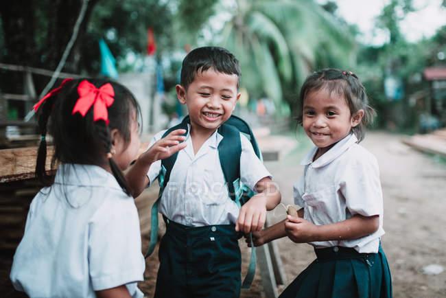 ЛАОС, 4000 ОСТРОВ АРЕЯ: Веселые дети в школьной форме стоят на деревенской улице и смеются . — стоковое фото