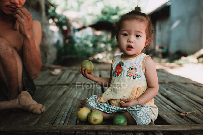 NONG KHIAW, LAOS: Pretty girl sitting on wooden doorstep in village and holding fruit. — Stock Photo