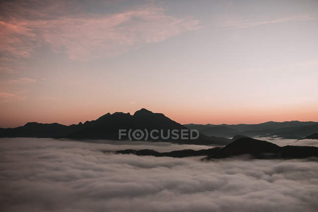 Cloudscape amid mountain peaks over sunset sky — Stock Photo