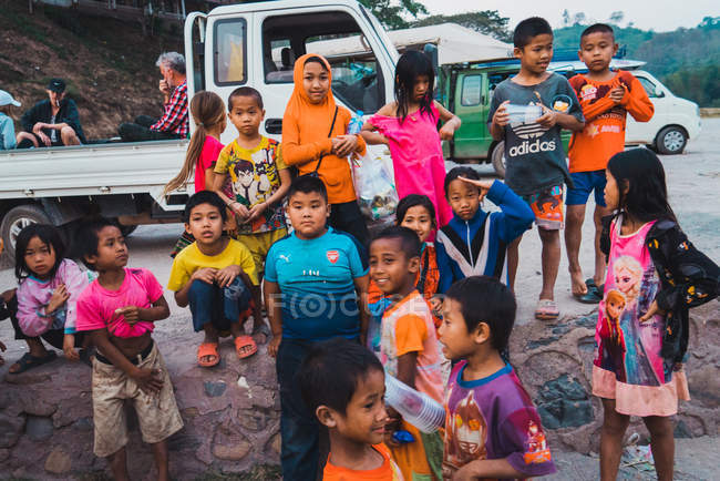 Лаос-18 лютого 2018: Група веселий азіатські діти веселяться і стоячи на вантажні автомобілі. — стокове фото