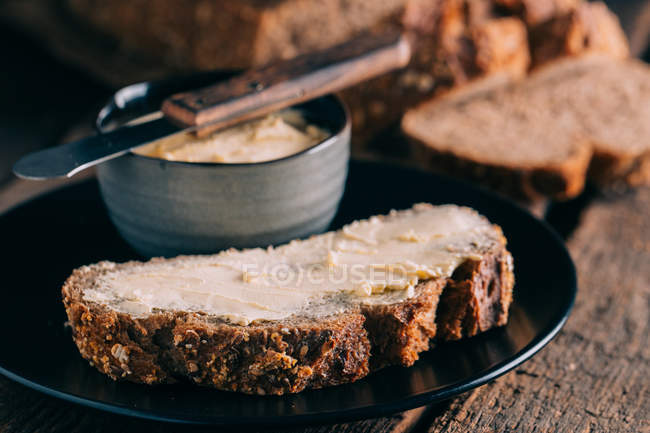 Close up view of rustic bread with butter — Stock Photo