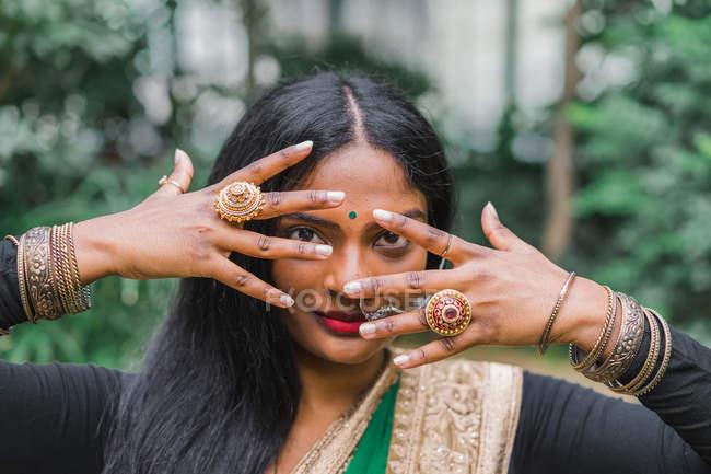 Молода жінка етнічних у традиційний одяг постановки в саду. — стокове фото