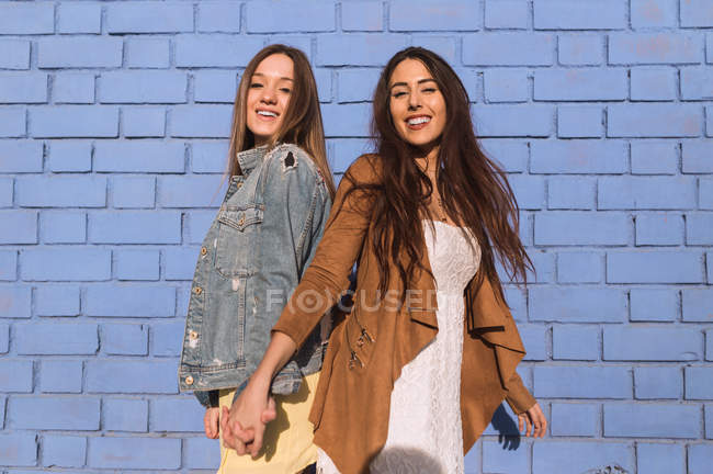 Cheerful young women standing and embracing at blue brick wall. — Stock Photo