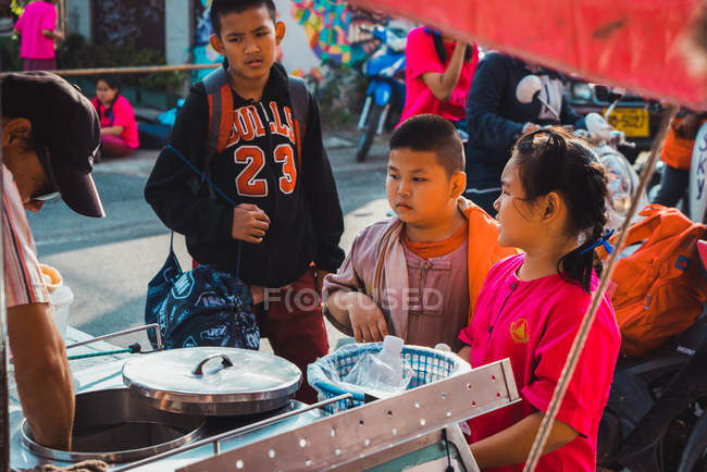 CHIANG RAI, THAILAND- FEBRUARY 9, 2018: Young Asian teenagers standing on town street and buying food. — Stock Photo