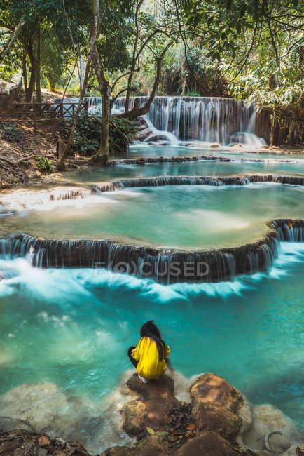 Вид сзади на сидящего туриста у тропического водопада — стоковое фото