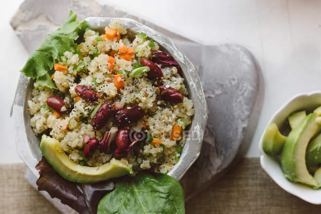 Салат из киноа и красной фасоли в миске на столе — стоковое фото