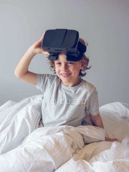 Улыбающийся мальчик лежит на кровати и снимает очки — стоковое фото