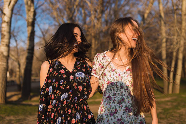 Two smiling young girls standing in sunny woods together. — Stock Photo