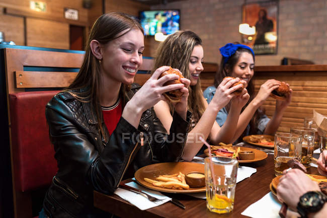 Cheerful young women eating burgers together in restaurant. — Stock Photo